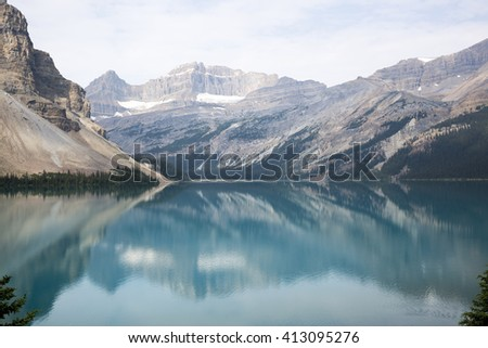Blue-green lake surrounded by mountains in Canada, mountains reflected in the water - stock photo