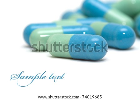 Blue-green pills isolated over white - stock photo