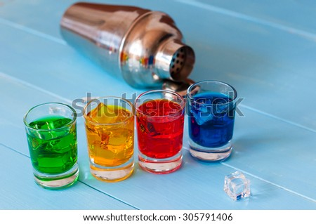 Blue, green, red alcohol or alcohol-free cocktail with ice cubes and shaker on a bar counter, wooden background - stock photo