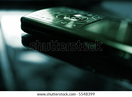 Blue/green toned picture of a mobile phone (shallow DoF, focused on round central button) - stock photo