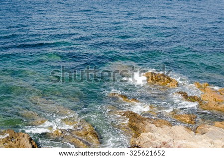 Blue, green, turquoise sea with rocks and waves - stock photo