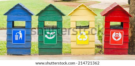 Blue, green, yellow and red bins on stand near footpath in park. - stock photo