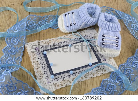 Blue greeting card with blue booties - stock photo