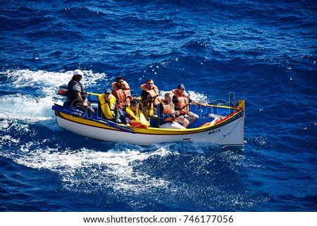 BLUE GROTTO, MALTA - APRIL 1, 2017 - Tourists in Dghajsa water taxi boat in the bay, Blue Grotto, Malta, Europe, April 1, 2017.