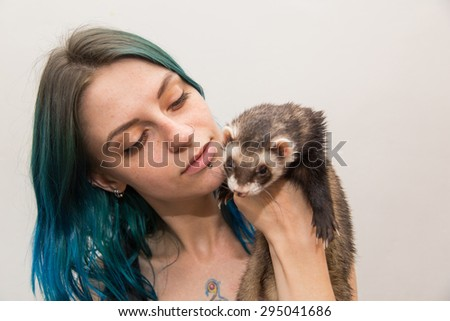 blue haired pretty girl plays with ferret