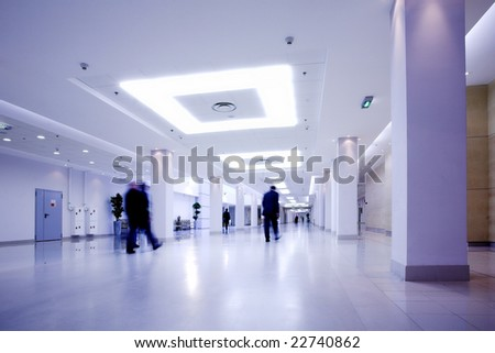 Blue hall of office centre, people move - stock photo