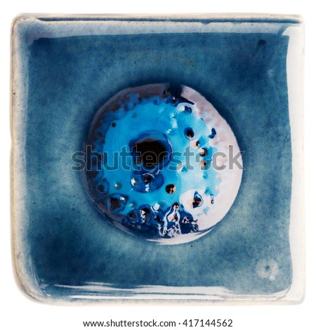 Blue handmade glazed ceramic tile with bubble in middle isolated on white