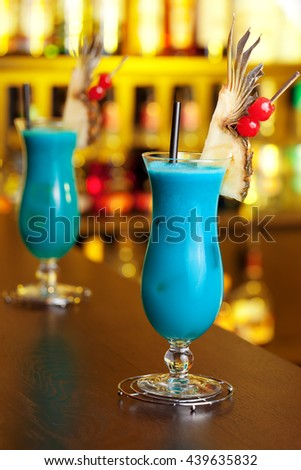 Blue Hawaiian cocktails shot on a bar in yellow light - stock photo