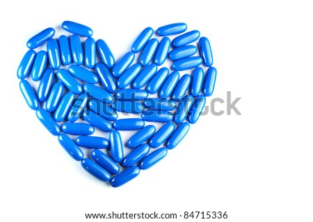 Blue heart by pill  isolated on white background - stock photo