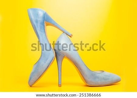 blue high heels shoes on yellow background - stock photo