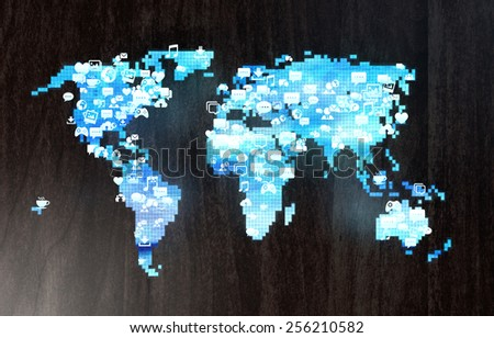 Blue holographic world map on a wooden desk with social media related glowing icons - stock photo
