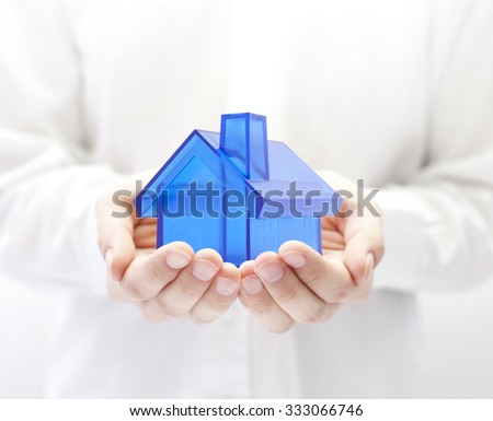 Blue house in hands. Home insurance concept. - stock photo