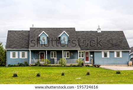Blue house with a porch and dormers - stock photo