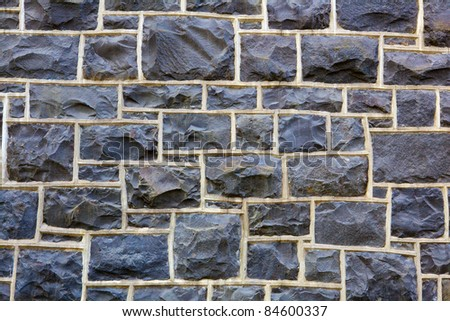 Blue hued rectangular shaped stone wall - stock photo