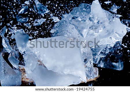 Blue ice cube exploding into small pieces on black background - stock photo