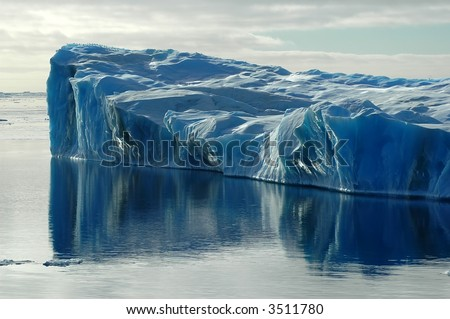 Blue iceberg with water reflection - stock photo