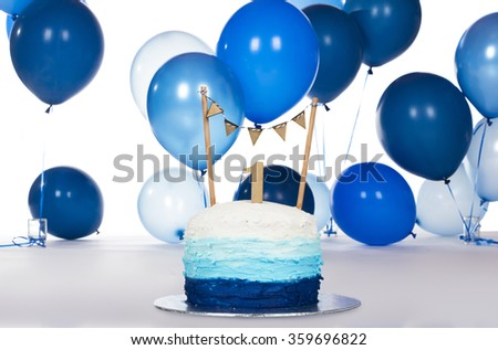 Blue iced birthday cake on a silver board with blue helium balloons in the background. - stock photo