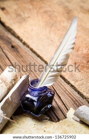 Blue ink with feather on old wooden table - stock photo