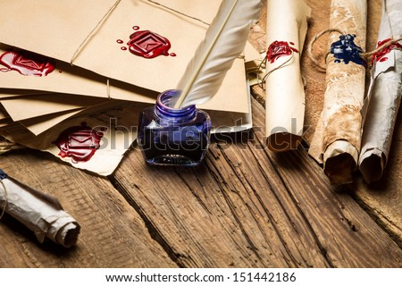 Blue inkwell and glasses on table filled with old messages - stock photo