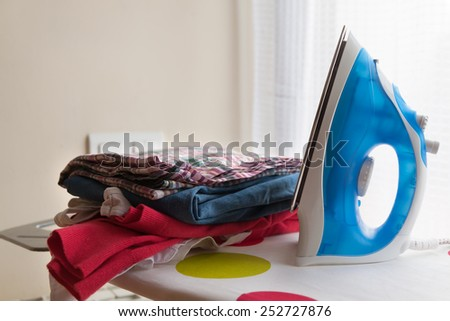 Blue iron on  ironing board with laundry - stock photo