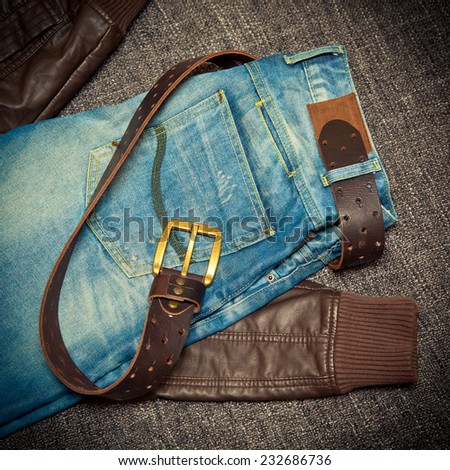 Blue jeans, a leather belt with a buckle and leather jacket - stock photo