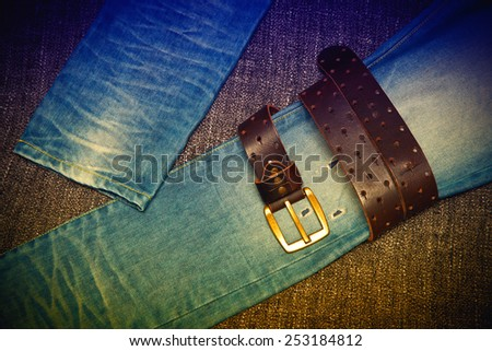 Blue jeans and a leather belt with a gold buckle. Youth trend. Photo toned in yellow and purple. - stock photo