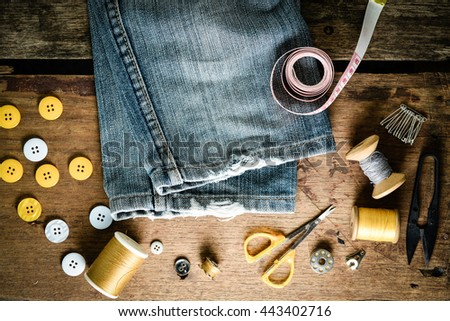 Blue jeans and sewing tools kit on wooden textured background - stock photo