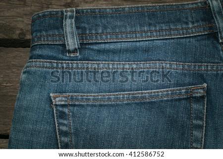 Blue jeans back pocket on wooden background. - stock photo