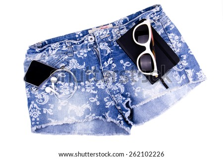 Blue jeans shorts, black paper notebook, sunglasses on white background, isolated. Mobile phone and modern earphones are in shorts pocket. - stock photo