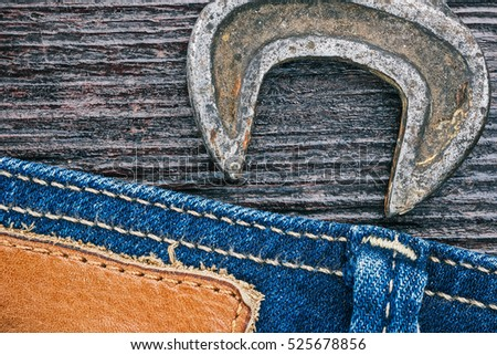 Blue jeans stitched edge and old metal wrench on dark wood. Everyday home repair background. Macro view