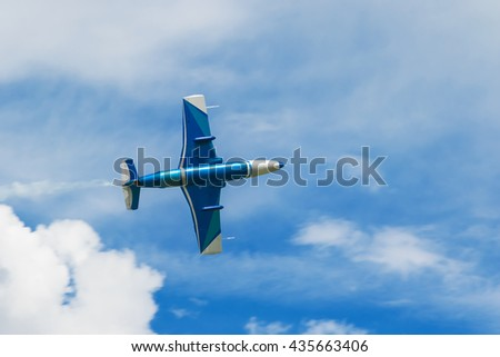 Blue jet plane jetting smoke flying in the blue sky with clouds closeup - stock photo