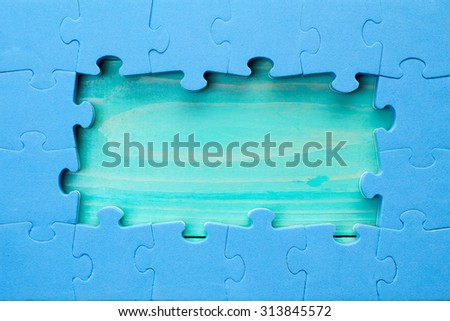 Blue jigsaw puzzle pieces arranged as a border around a green wooden surface   - stock photo
