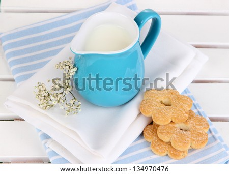 Blue jug with milk and cookies on wooden picnic table close-up - stock photo