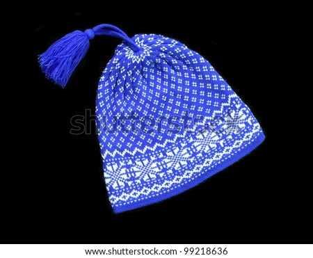 Blue knitted wool hat with pom pom isolated on black background - stock photo