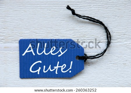 Blue Label Or Tag With Black Ribbon On White Wooden Background With German Text Alles Gute Which Means Best Wishes Vintage Retro Or Rustic Style - stock photo