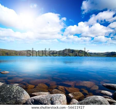 Blue lake idill under cloudline sky - stock photo
