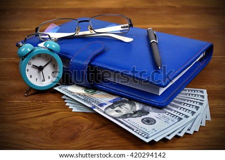 blue leather diary, glasses, pen and dollar bills on wooden desk. time is money concept - stock photo