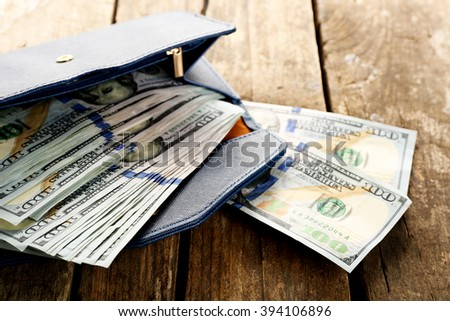 Blue leather wallet with money on wooden table