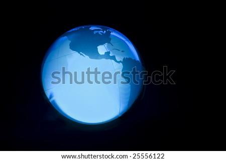 Blue light through a glass globe on a dark background - stock photo