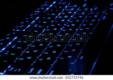 Blue lighting keyboard in the dark - stock photo