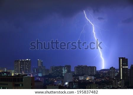 Blue Lightning. Thunderbolt hitting a hill beyond the city limits. Intense flash illuminating the cityscape . - stock photo