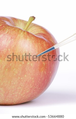 Blue liquid being injected into a Fuji apple. Studio shot. - stock photo