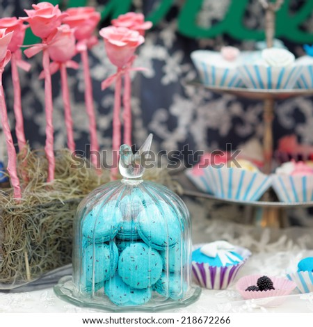 Blue macaroons in glass jar and cupcakes on stylish sweet table - stock photo