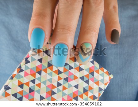 Blue manicure in light and dark colors of lacquer on a striped background. - stock photo
