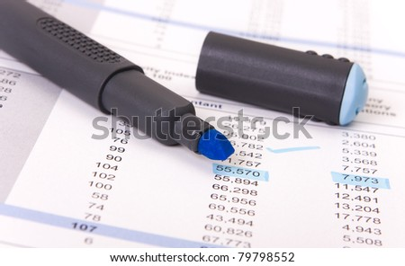 Blue marker and a report sheet with numbers underlined - stock photo