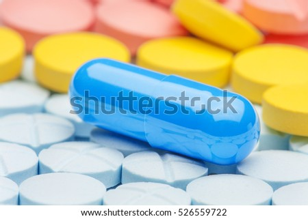 blue medical pill on a background of yellow and red pills