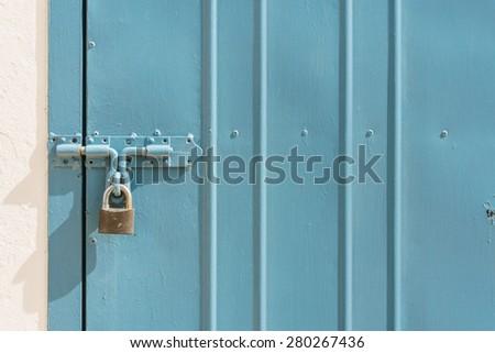 blue metal door with padlock, texture and background - stock photo