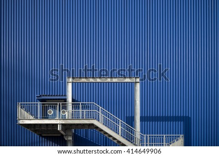 Blue metal sheet warehouse with back door ladder. - stock photo