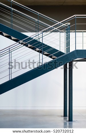 Blue metal staircase. Interior warehouse stairs. Emergency exit stairs.