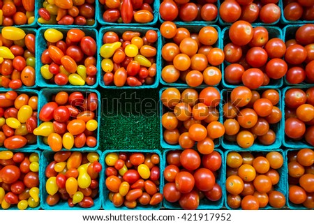 Blue mini produce cartons with various small tomato varieties laid out in an orderly grid with one carton missing.